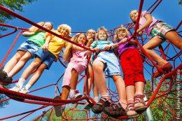 Klettergeräte benötigen eine Prüfpficht, das Bild zeigt Kinder die alle gemeinsam auf einem Klettergerät stehen.