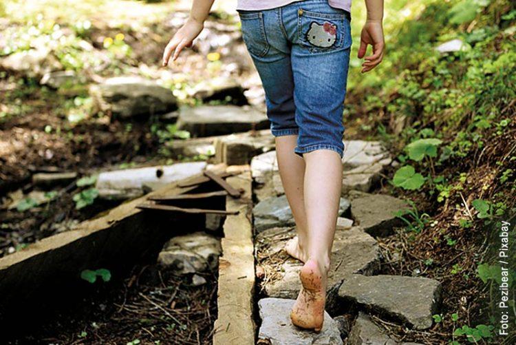 Sichere Wege auf dem Spielplatz - was muss beachtet werden? Das Bild zeigt ein Kind das barfuß über Steinplatten läuft.